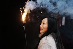 Muchacha china asiática que sostiene el fuego artificial de la bengala con la mano en el fondo negro Morenita, mirando Imagen de archivo