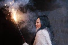 Muchacha china asiática que sostiene el fuego artificial de la bengala con la mano en el fondo negro Morenita, mirando Imagen de archivo libre de regalías