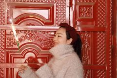 Muchacha china asiática que sostiene el fuego artificial de la bengala con la mano en el frente de la puerta roja Morenita, miran Fotografía de archivo