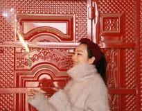 Muchacha china asiática que sostiene el fuego artificial de la bengala con la mano en el frente de la puerta roja Morenita, miran Imagen de archivo libre de regalías