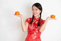 Muchacha china asiática que sostiene la mandarina anaranjada Foto de archivo libre de regalías