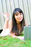 Muchacha china asiática que usa la computadora portátil Imagenes de archivo