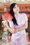Muchacha china con el sobre en el templo Foto de archivo libre de regalías