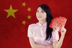 Muchacha china con el sobre y la bandera de China Fotografía de archivo