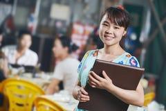 Muchacha china de la camarera del restaurante con el menú Imagenes de archivo