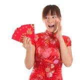 Muchacha china del cheongsam de la sorpresa que sostiene los paquetes rojos Imágenes de archivo libres de regalías