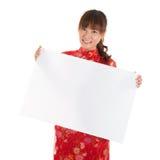 Muchacha china del cheongsam que lleva a cabo el cartel Foto de archivo
