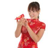 Muchacha china del cheongsam que mira a escondidas en los paquetes rojos Fotos de archivo
