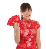 Muchacha china del cheongsam que muestra los paquetes rojos Fotos de archivo