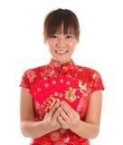 Muchacha china del cheongsam que sostiene los paquetes rojos Fotografía de archivo
