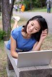 Muchacha china hermosa feliz con la computadora portátil Foto de archivo