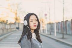 Muchacha china hermosa joven con los auriculares Foto de archivo libre de regalías