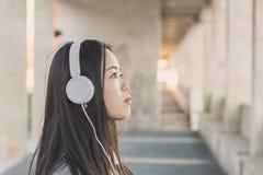 Muchacha china hermosa joven con los auriculares Fotos de archivo libres de regalías