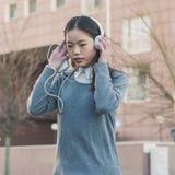 Muchacha china hermosa joven con los auriculares Imagenes de archivo