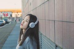 Muchacha china hermosa joven con los auriculares Foto de archivo