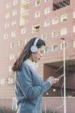 Muchacha china hermosa joven con los auriculares Imagen de archivo
