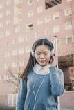 Muchacha china hermosa joven con los auriculares Imagen de archivo libre de regalías