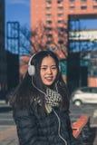 Muchacha china hermosa joven con los auriculares Imágenes de archivo libres de regalías