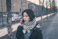 Muchacha china hermosa joven que habla en el teléfono en las calles de la ciudad Foto de archivo libre de regalías