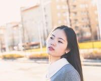 Muchacha china hermosa joven que presenta en las calles de la ciudad Imágenes de archivo libres de regalías
