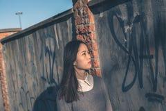 Muchacha china hermosa joven que presenta en las calles de la ciudad Fotografía de archivo