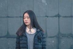Muchacha china hermosa joven que presenta en las calles de la ciudad Imagenes de archivo