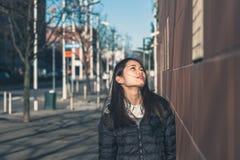 Muchacha china hermosa joven que presenta en las calles de la ciudad Imagen de archivo
