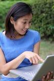 Muchacha china hermosa sorprendida sobre la computadora portátil Fotos de archivo libres de regalías