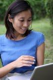 Muchacha china hermosa sorprendida sobre la computadora portátil foto de archivo