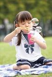 Muchacha china joven en burbujas que soplan del parque Imagenes de archivo