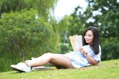 Muchacha china que lee el libro Mujer joven hermosa rubia con el libro que miente en la hierba Foto de archivo