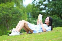 Muchacha china que lee el libro Mujer joven hermosa rubia con el libro que miente en la hierba Imagen de archivo libre de regalías