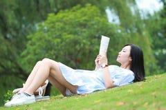 Muchacha china que lee el libro Mujer joven hermosa rubia con el libro que miente en la hierba Imagenes de archivo