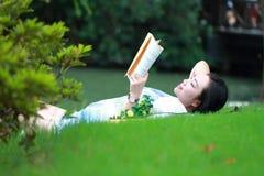 Muchacha china que lee el libro Mujer joven hermosa rubia con el libro que miente en la hierba Fotos de archivo libres de regalías