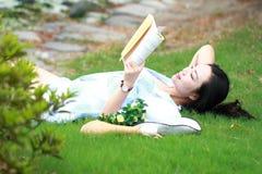 Muchacha china que lee el libro Mujer joven hermosa rubia con el libro que miente en la hierba Imagen de archivo