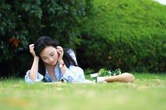 Muchacha china que lee el libro Mujer joven hermosa rubia con el libro que miente en la hierba Imágenes de archivo libres de regalías