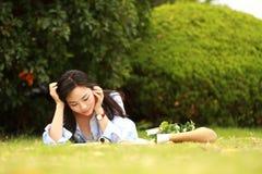 Muchacha china que lee el libro Mujer joven hermosa rubia con el libro que miente en la hierba Foto de archivo libre de regalías