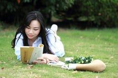 Muchacha china que lee el libro Mujer joven hermosa rubia con el libro que miente en la hierba Fotografía de archivo libre de regalías