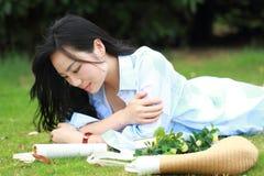 Muchacha china que lee el libro Mujer joven hermosa rubia con el libro que miente en la hierba Fotos de archivo