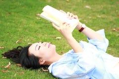 Muchacha china que lee el libro Mujer joven hermosa rubia con el libro que miente en la hierba Fotografía de archivo