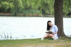 Muchacha china que lee un libro debajo de árbol La mujer joven hermosa rubia con el libro se sienta en la hierba Imágenes de archivo libres de regalías