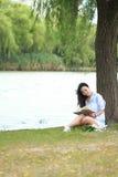 Muchacha china que lee un libro debajo de árbol La mujer joven hermosa rubia con el libro se sienta en la hierba Fotografía de archivo libre de regalías