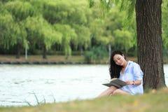 Muchacha china que lee un libro debajo de árbol La mujer joven hermosa rubia con el libro se sienta en la hierba Imagenes de archivo