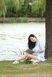 Muchacha china que lee un libro debajo de árbol La mujer joven hermosa rubia con el libro se sienta en la hierba Foto de archivo libre de regalías