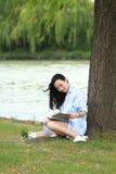 Muchacha china que lee un libro debajo de árbol La mujer joven hermosa rubia con el libro se sienta en la hierba Fotografía de archivo