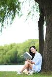 Muchacha china que lee un libro debajo de árbol La mujer joven hermosa rubia con el libro se sienta en la hierba Foto de archivo