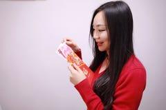Muchacha china que lleva a cabo el control rojo de la mujer de los paquetes con el dinero afortunado Foto de archivo