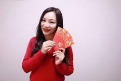 Muchacha china que lleva a cabo el control rojo de la mujer de los paquetes con el dinero afortunado Imagen de archivo libre de regalías