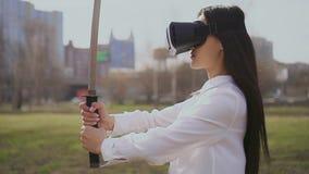 Muchacha china que mira la espada usando los vidrios de la realidad virtual Soplos del viento en el pelo metrajes