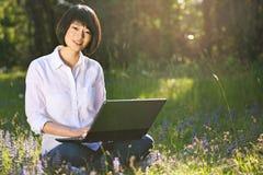 Muchacha china sonriente con el ordenador portátil en el parque Foto de archivo